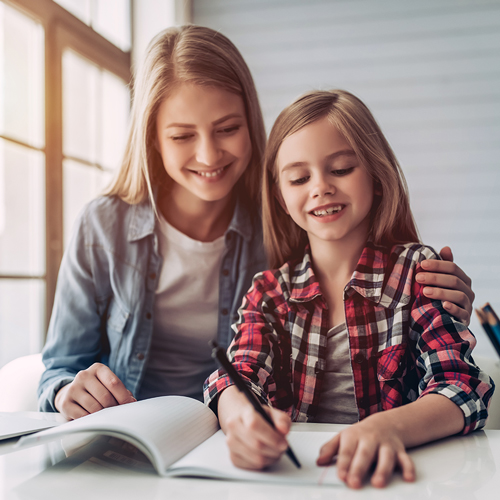Mother and daughter smiling while writing